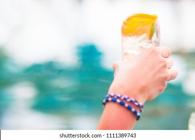 man holding jin tonic cocktail topped with orange by the pool