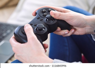 man holding a joystick controllers while playing a video games at home