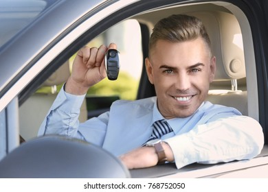 Man holding key when sitting on driver's seat of car