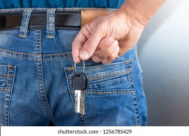 man holding keys in hand. Person taking keys out of pocket. male hides key behind his back.