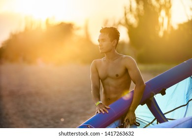 Man holding a kite in hands standing at the beach on sunset after a good kiteboarding session. Kitesurfer with wing enjoys kitesurfing on tropical island. Athletic guy with abs going to deflate kite.