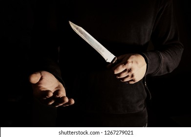 Man holding knife in hands and demanding money. Robber in black sweater. Dangerous people. Be careful concept.