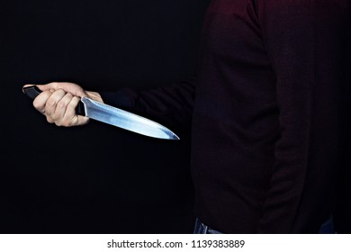 Man holding a knife near his belly, suicide, black background, stomach