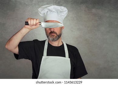 man holding knife on gray background
