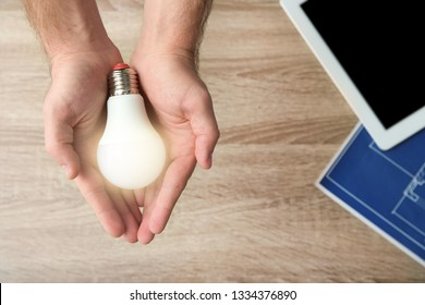 Man holding lamp bulb over table with tablet and blueprint, top view. Space for text