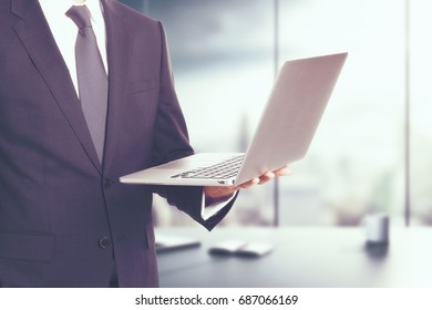 Man holding laptop on blurry office background with city view. Communication concept