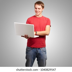 Man Holding Laptop On Gray Background