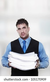 man holding a large pile of paper work in his arms has lot of work to do