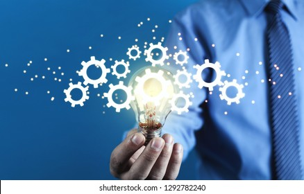 Man holding light bulb and gears mechanism. Concept of Idea, Imagination, Creativity