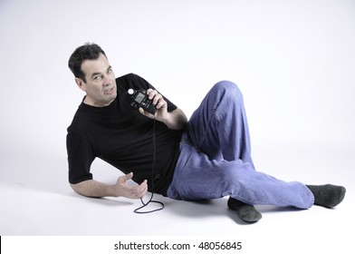Man holding light meter with the readings towards the camera.He is on a seamless white background.
