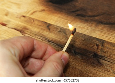 A man holding a lit match. This image also contains a wooden background and can be used to represent fire starting or arson.
