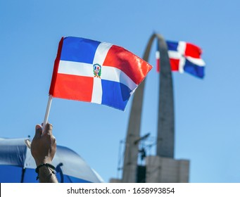 A man holding a little Dominican flag with the flag monument (plaza de la bandera) in the background