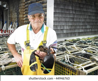 Man holding lobster and facing the camera.  Lobster traps in the background. Horizontal shot.