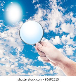 Man holding magnifying glass with cloudy sky in the background