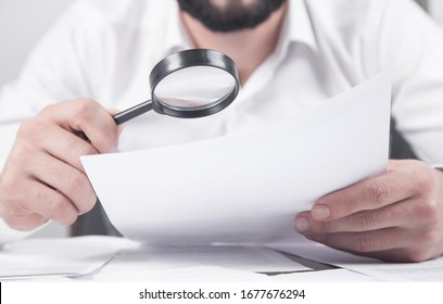 Man holding magnifying glass with documents.