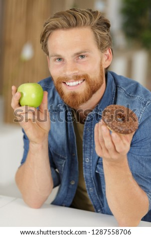 man holding and making choice between healthy or junk-food