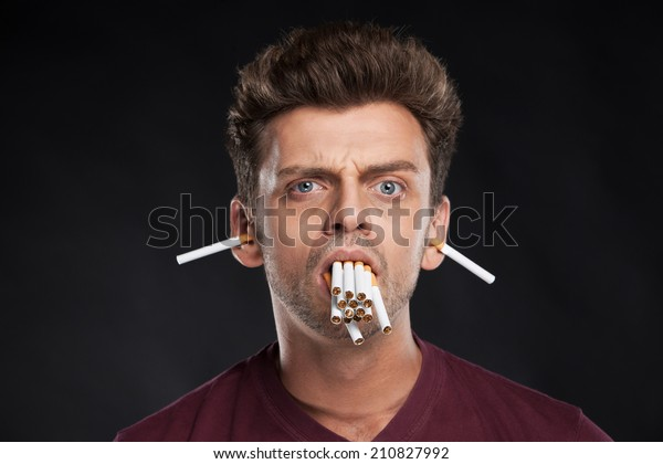Man holding many cigarettes in his mouth. Man gone crazy with many cigarettes in mouth