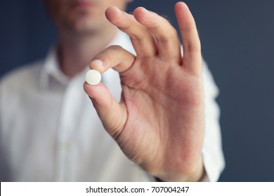 Man holding medicine. Hand of person showing white pill towards camera.