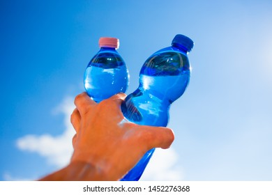 man holding the mineral water in plastic bottle with blue sky in the background, in strong backlight