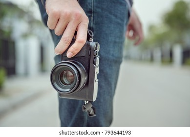 Man holding mirrorless camera travel photo of photographer Making pictures in hipster style
