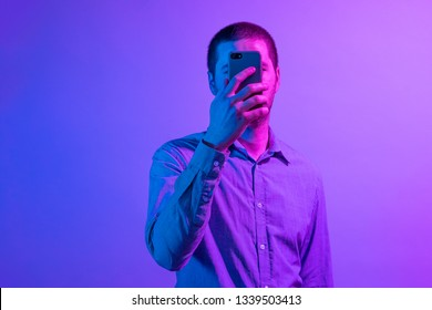 Man holding a mobile in front of his face as though short-sighted side lit by colorful pink through purple to blue lighting