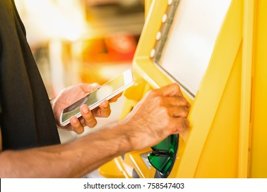 Man holding mobile phone and entering number on atm machine to withdraw or transfer money