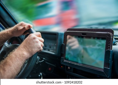 man holding mobile phone with gps application in the car with tablet screen computer Sun light on finger Sunset rays on hands Male inside brutal SUV car against truck.No face.Unrecognizable person