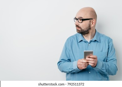 Man holding a mobile phone looking to the side as he stands leaning against a white wall with copy space