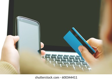 Man holding mobile phone in one hand and credit card in another hand. Laptop visible.