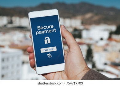 Man holding mobile phone. Secure payment notification in the screen.