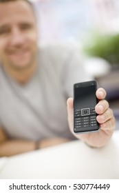 Man holding a mobile phone, smiling
