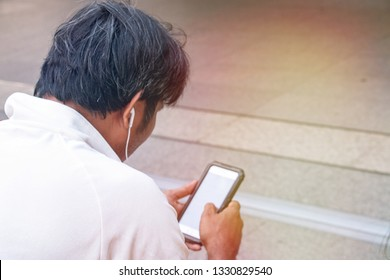 Man is holding mobile phone and wears head set