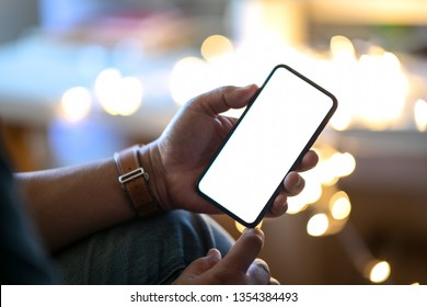 Man holding mobile smart phone at street night with blurred background