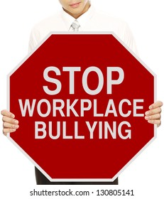 A man holding a modified stop sign on workplace bullying