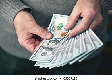 the man holding money dollars banknotes of one hundred