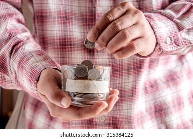 man holding money jar with coins close up