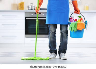 Man holding mop and plastic bucket with brushes, gloves and detergents in the kitchen
