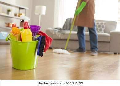 Man holding mop and plastic bucket