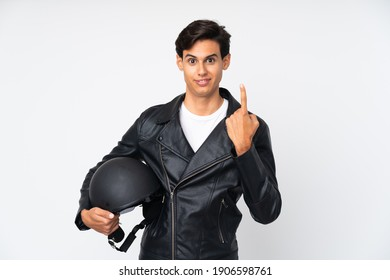 Man holding a motorcycle helmet over isolated white background pointing with the index finger a great idea