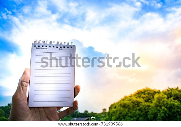 Man holding notepad on tree blurry background.using wallpaper for education, business photo.Take note of the product for book with paper and concept, object or copy space.