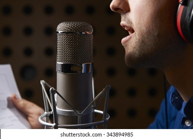 Man Holding Notes And Talking Into Studio Microphone