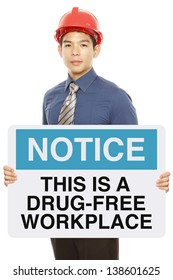 A man holding a notice sign announcing a drug-free workplace