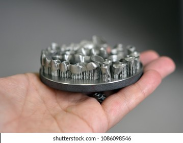 Man is holding object printed on metal 3d printer. Dental crowns created in laser sintering machine close-up. DMLS, SLM, SLS technology. 4.0 industrial revolution. Progressive modern additive technol
