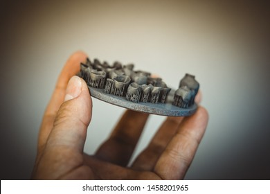 Man holding object printed on metal 3d printer after heat treatment synterization close-up. Dental crowns created in laser sintering machine. DMLS, SLM, SLS technology. 4.0 industrial revolution.