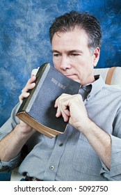 A man holding an old bible, with an expression of contemplation on his face.