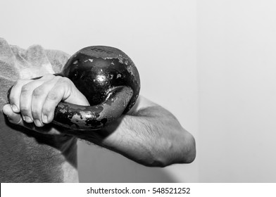 Man holding old and rusty kettlebell on his shoulder.