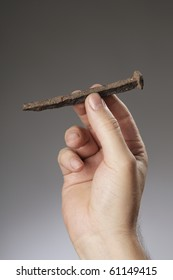 Man holding an old rusty nail in his hand