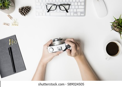 Man is holding an old vintage film camera over the white desk table. Top view, flat lay.