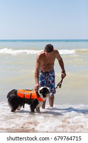 Man holding onto his older dog  in a life jacket as he prepares to swim at the Pinery provincial park on Lake Huron in Ontario Canada
