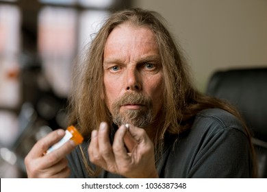 Man holding an opiod pill